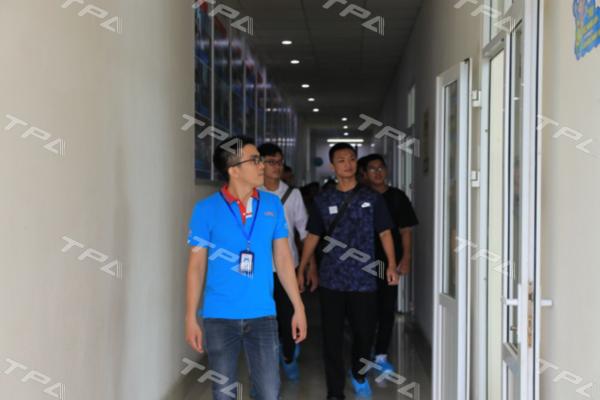 Nhân viên TPA dẫn các em sinh viên xuống xưởng sản xuất TPA